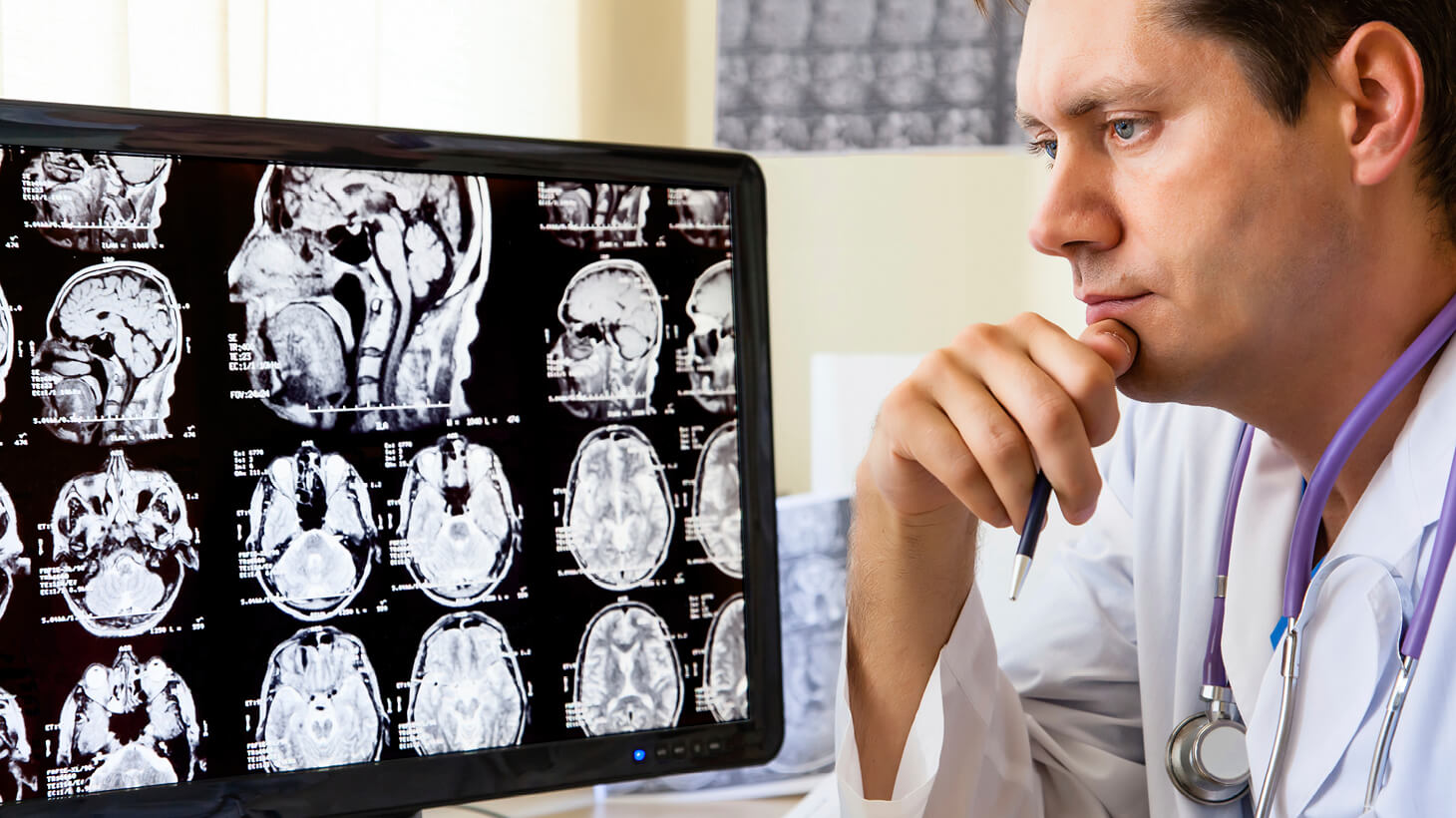 Doctor reviewing scans on computer monitor