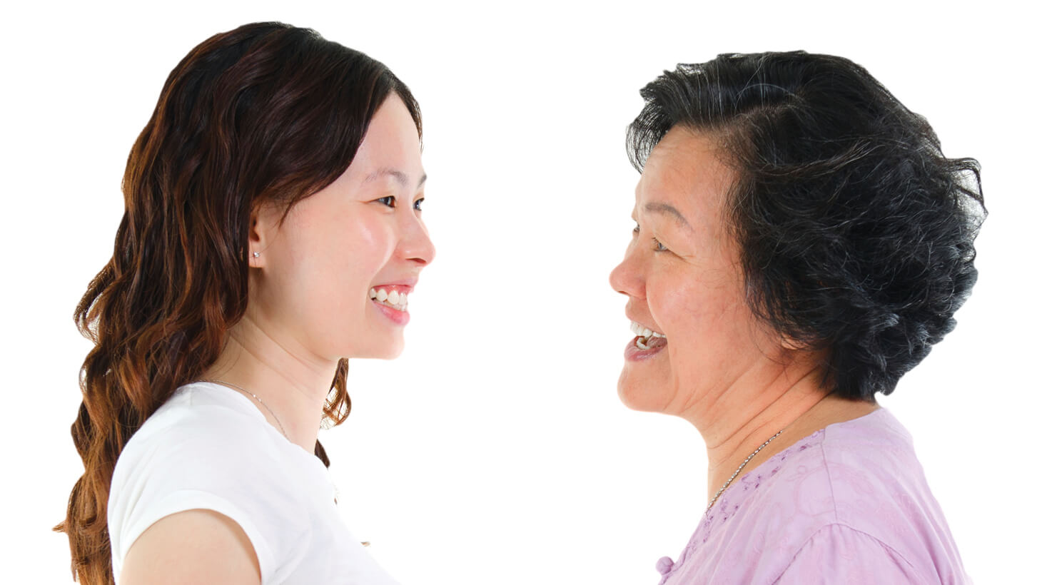 Senior Asian mother and her adult daughter facing each other in profile and smiling warmly